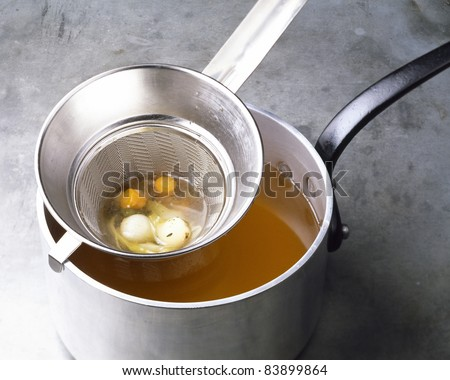 Passing the vegetables through a sieve - stock photo