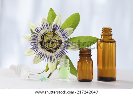 Passion flower with aromatherapy essential oil glass - stock photo