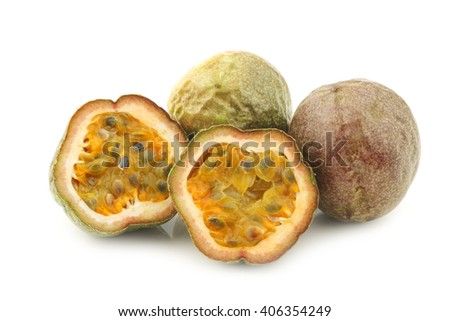 passion fruits and a cut one on a white background - stock photo