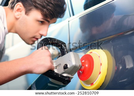 Passionate about cars. Portrait of a handsome smiling car mechanic polishing the luxury car with an orbital polisher in car repair shop - stock photo