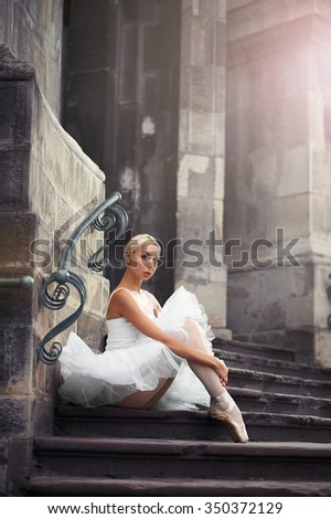 Passionate about dance. Cropped shot of a gorgeous female ballet dancer posing outdoors sitting near an old building looking to the camera soft focus  - stock photo