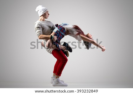 Passionate attractive casual couple dancing. Two modern style beautiful dancers working out. Young man holding his girl partner. Full length image, studio gray background