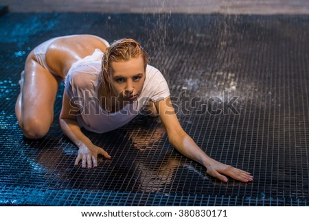 Passionate beautiful young woman enjoying pleasant shower, creeping on the floor in wet panties and t-shirt and looking at camera - stock photo