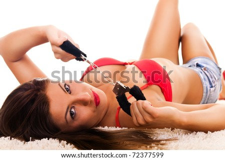 Passionate brunette playing with the handcuffs - stock photo