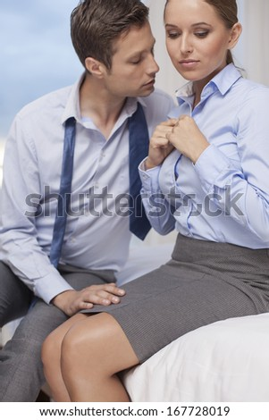 Passionate business couple in hotel room - stock photo