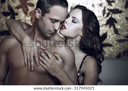 Passionate couple foreplay at night in luxury hotel room - stock photo