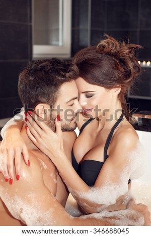 Passionate couple foreplay in jacuzzi, kissing