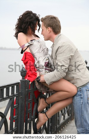 passionate dating a beautiful young couple on the embankment - stock photo