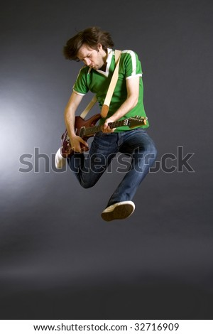 passionate guitarist jumps in the air - stock photo