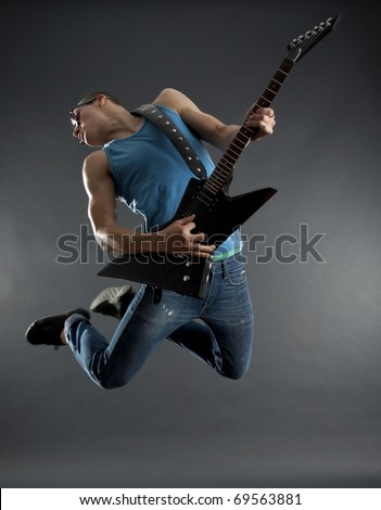 passionate guitarist jumps in the air over black - stock photo