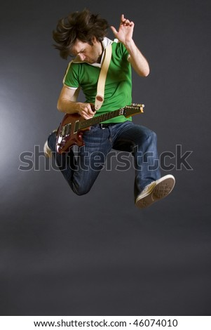 passionate guitarist jumps in the air over dark background - stock photo