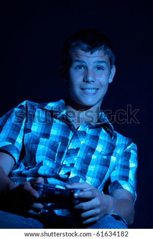 Passionate playing with a console, under the reflection of the screen - stock photo