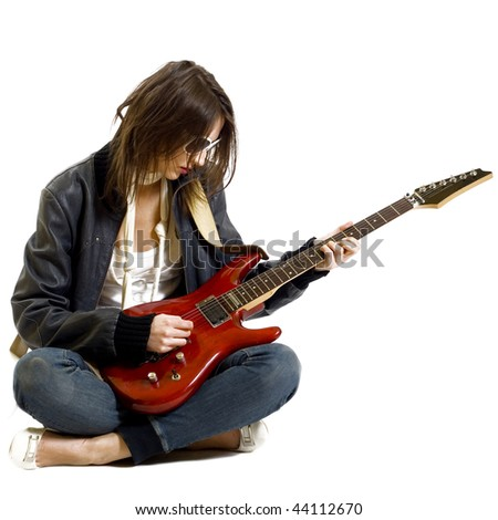 passionate rock girl playing an electric guitar sitting down