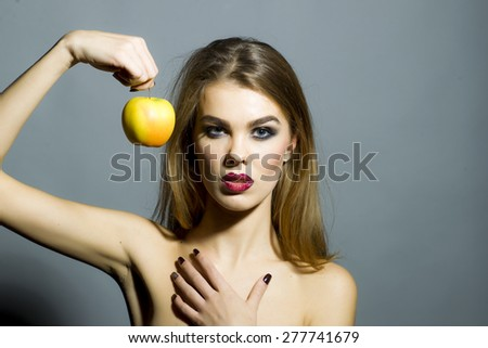 Passionate sensual woman with bright make up looking forward holding fresh yellow apple standing on gray background copyspace, horizontal picture - stock photo