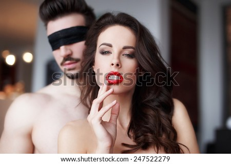 Passionate sensual woman with red lips in hotel room with lover, couple foreplay - stock photo