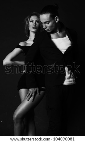 Passionate sexual couple posing semi naked on dark background