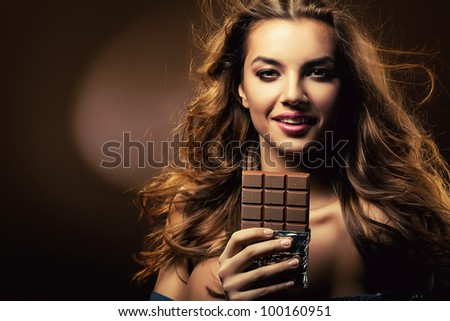 passionate smiling woman and chocolate block - stock photo