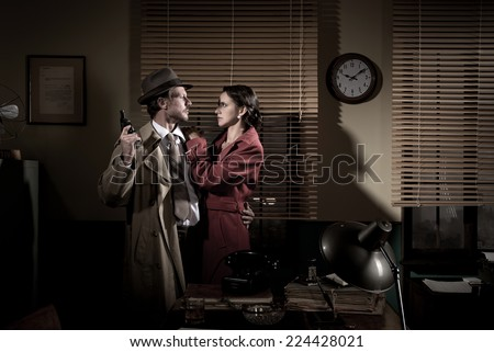 Passionate vintage couple embracing in detective's office holding a gun. - stock photo
