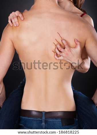 Passionate woman's hand scratching shirtless man's back over black background - stock photo