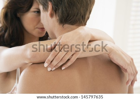 Passionate young couple embracing in bedroom - stock photo