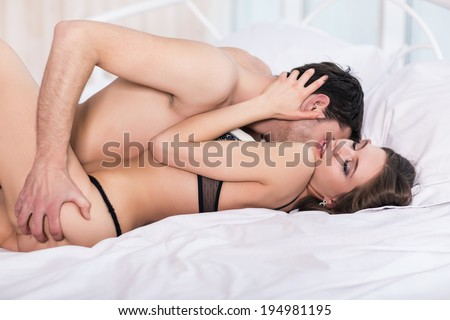 Passionate young couple in bed - stock photo