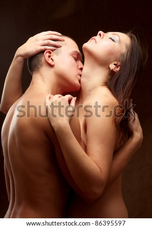 Passionate young couple isolated on brown - stock photo