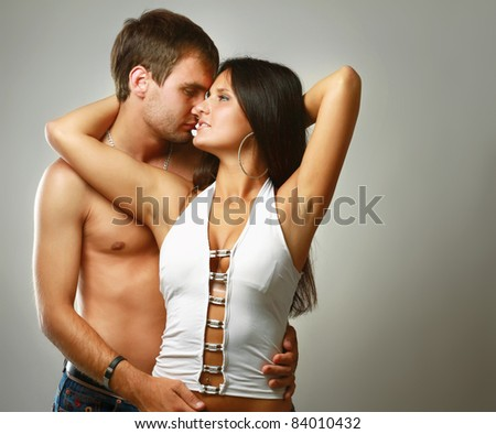 Passionate young couple isolated on grey - stock photo