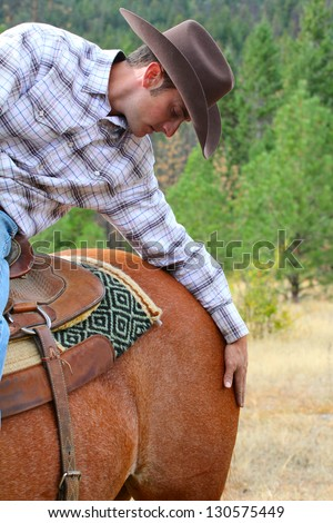 Passionate young cowboy spending time with his horse - stock photo