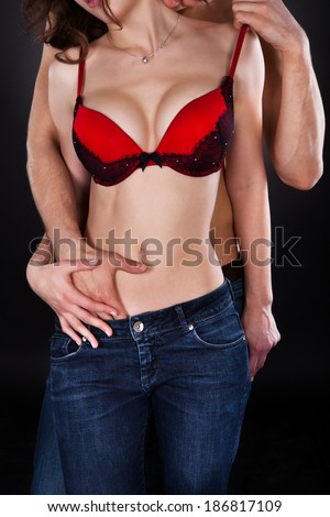Passionate young man inserting hand in woman's jeans while kissing her on neck isolated over black background - stock photo