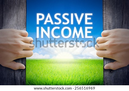 Passive Income. Hand opening an old wooden door and found Passive Income word floating over green field and bright blue Sky Sunrise. - stock photo