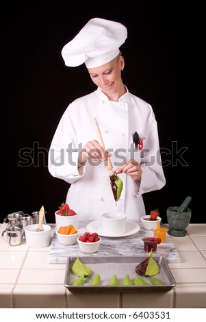Passive posed uniformed female Pastry Chef standing at her dessert station brushing melted dark chocolate onto a citrus leaf.