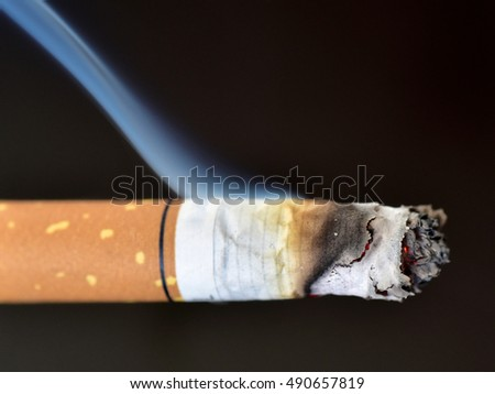 Passive smoking is also injurious to health. Blue smoke from a burning cigarette against black background. Thick fume from a cigarette.