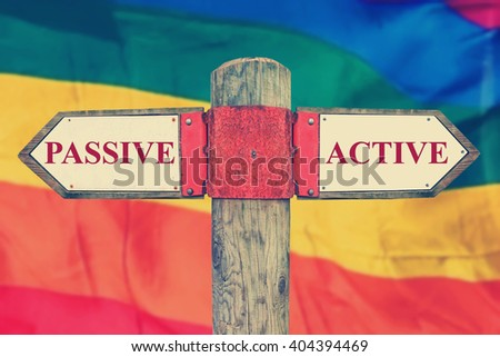 Passive versus Active messages - Wooden signpost with two opposite arrows with rainbow gay pride flag fluttering blur background. Toned colors vintage style image - stock photo