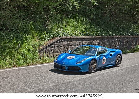 "PASSO DELLA FUTA (FI), ITALY - MAY 21: driver and co-driver on a sports car Ferrari 488 Spider (2016) in rally ""Ferrari tribute to Mille Miglia"" on May 21, 2016 in Passo della Futa (FI) Italy"