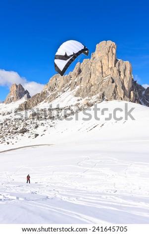 PASSO GIAU, ITALY - MARCH 11, 2012 - Snow kiter bording on snow in Passo Giau, Italy on a sunny winter day. - stock photo