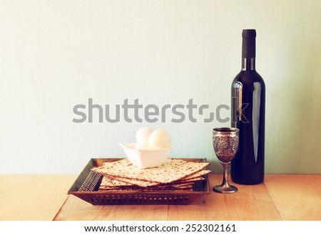 Passover background. wine and matzoh (jewish holiday bread) over wooden board. - stock photo