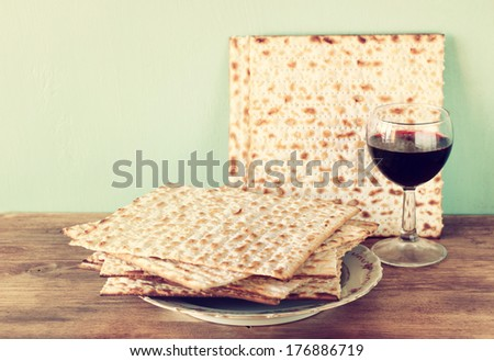 passover background. wine and matzoh (jewish passover bread)  over wooden background. vintage effect process. - stock photo