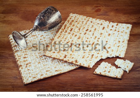 Passover background. wine cup and matzoh (jewish holiday bread) over wooden table.