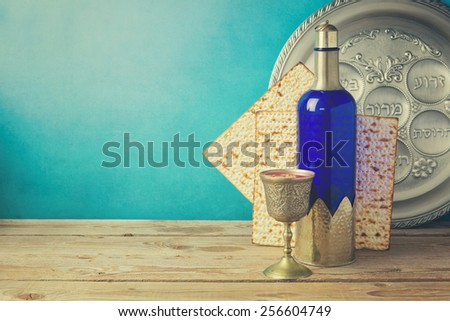 Passover background with matzo and wine on wooden vintage table. Seder plate with hebrew text says bone, lettuce, apple and nuts. - stock photo