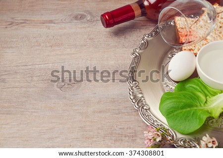 Passover (pesah) background with seder plate, matzoh and wine over wooden background - stock photo