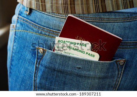 Passport and air boarding passes in jeans pocket - stock photo