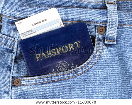 Passport and boarding pass sticking out of blue jeans pocket.