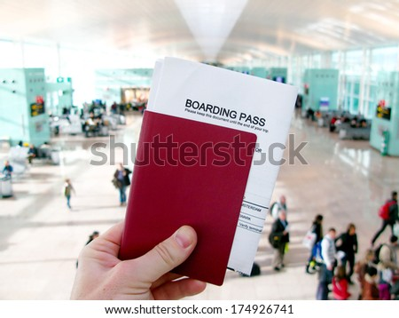 Passport and boarding pass, waiting for a flight in a modern airport - stock photo