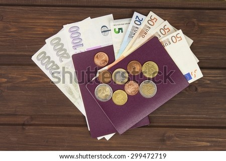 Passport and money on wooden table. Valid EURO banknotes, coins and banknotes Czech. Illegal migration for money. Paying smugglers for crossing the border.  - stock photo