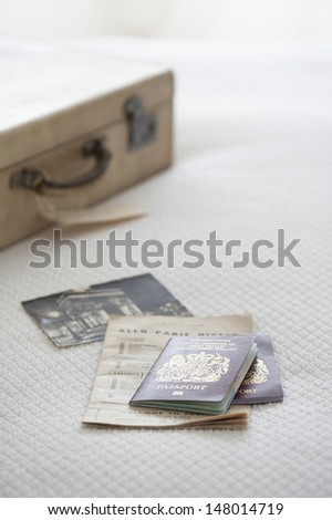 Passport and tickets with suitcase on bed - stock photo