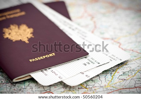 Passport book and tickets on a road map - stock photo