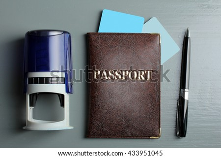 passport credit card near the print and pen on grey wooden background - stock photo