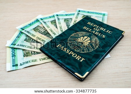 Passport of Republic of Belarus in green cover with Belarusian rubles lying on wooden table.