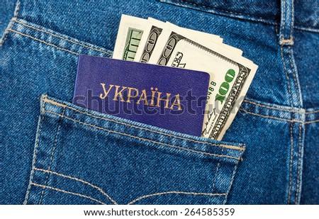 Passport of Ukraine and dollar banknotes in the back jeans pocket. Text in Ukrainian: Ukraine - stock photo