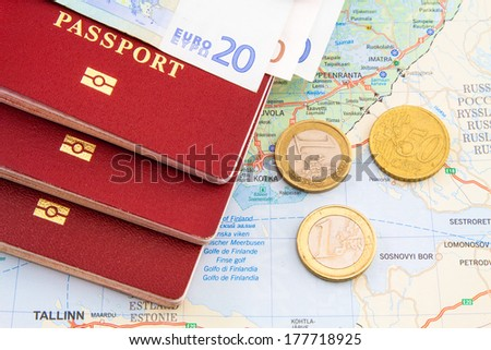passport on the map with coins and money - stock photo